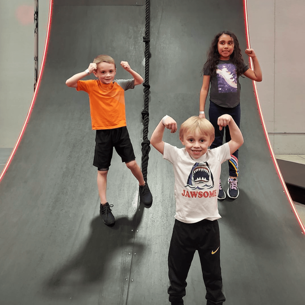 Three children pose for a photo at Adrenaline Monkey.