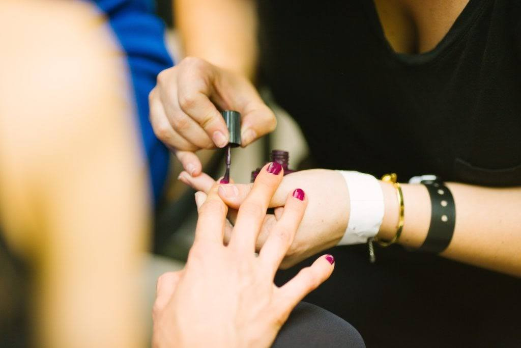 women painting finger nails.