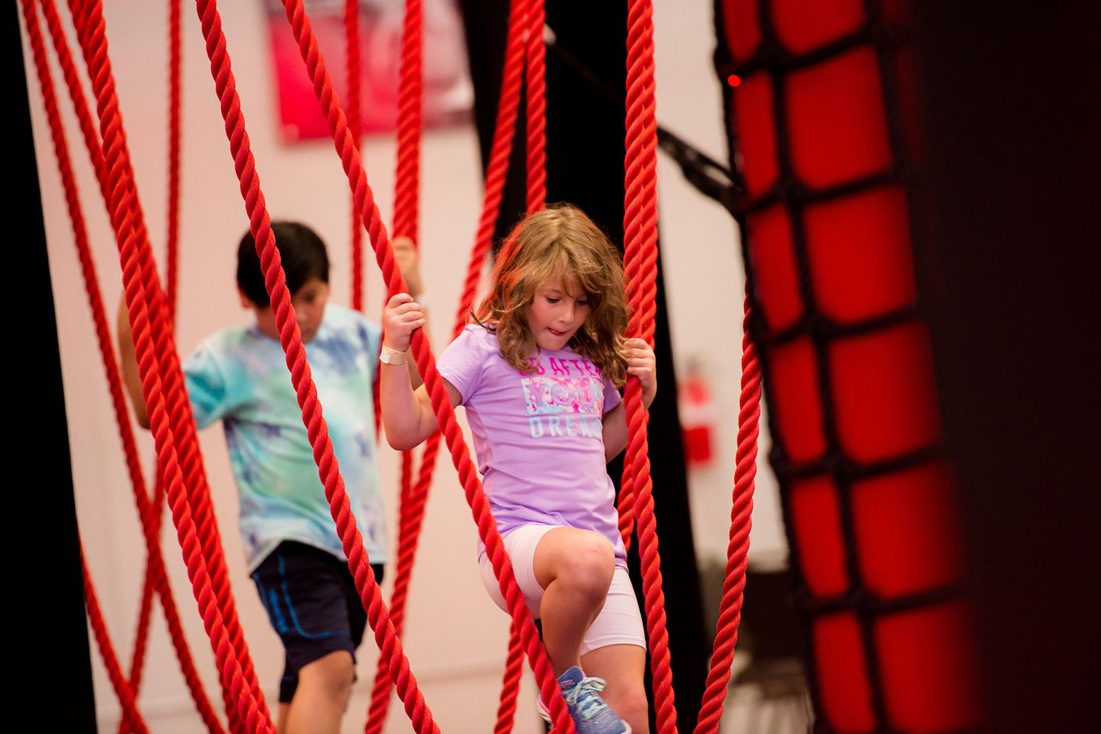 A young girl playing on an Adrenaline Monkey ropes obstacle